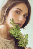 Portrait of woman with branch of green leaves Stock Photo