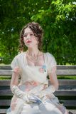 Portrait of woman in bride dress with a book in their hands. Portrait of a young bride woman in a historical white dress with a book in hands outdoors in a park Stock Photography