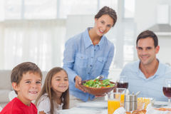 Portrait of a woman bringing a salad to her family Stock Photo