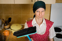 Portrait of Woman with a Broom in the Kitchen Stock Images