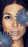 Portrait of woman brunette with Christmas decorations silver blue snowflakes. Fashion make-up. royalty free stock photography