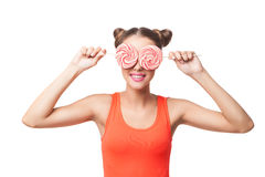 Portrait of woman with buns holding lollipops on eyes Royalty Free Stock Image