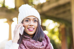 Portrait of woman with cap talking by smart phone, outdoor. royalty free stock photo