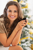Portrait of woman with cell phone near christmas tree Stock Images