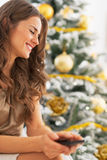 Portrait of woman with cell phone near christmas tree Stock Photography