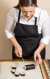 Portrait of woman chef cutting japanese sushi roll Royalty Free Stock Photo