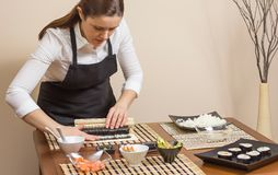 Portrait of woman chef rolling up a japanese sushi Royalty Free Stock Images