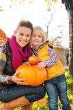 Portrait of woman and child holding pumpkins in autumn outdoors Royalty Free Stock Photos