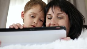 Portrait of a woman and a child. A mother and a little boy use a tablet computer to call, watch a movie, and access the. Internet. Close up stock footage