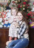 Portrait of a woman with a child near the Christmas tree. Mother with two year old daughter Royalty Free Stock Photo