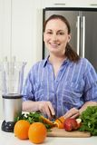 Portrait Of Woman Chopping Fruit To Put Into Juicer Royalty Free Stock Photography