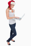 Portrait of a woman with a Christmas hat using a laptop Stock Image