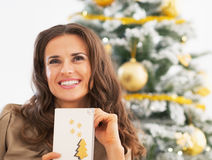 Portrait of woman and christmas postcard near christmas tree Royalty Free Stock Images