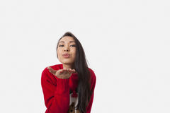 Portrait of woman in Christmas sweater blowing kiss over gray background Royalty Free Stock Photo