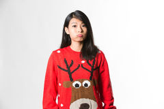 Portrait of woman in Christmas sweater standing making funny face over gray background.  stock photography