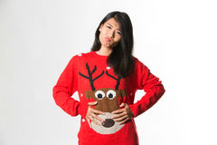 Portrait of woman in Christmas sweatershowing she has eaten too much food over gray background.  Stock Photography
