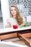 Portrait of woman with claret rose playing piano Royalty Free Stock Image