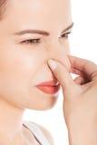Portrait of a woman clogging nose.  Stock Photo