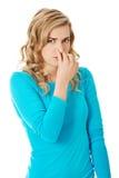 Portrait of a woman clogging nose.  Stock Photos
