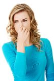 Portrait of a woman clogging nose Stock Images