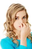 Portrait of a woman clogging nose.  Royalty Free Stock Photo