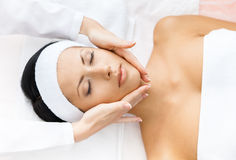 Portrait of woman with closed eyes getting face massage. Portrait of half-naked woman with closed eyes getting face massage. Concept of relax and medicine Royalty Free Stock Images