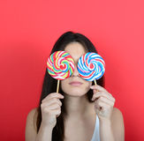 Portrait of woman covering eyes with lollipops against red backg Stock Image