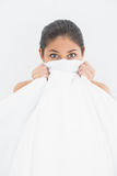 Portrait of a woman covering face with bedsheet in bed Royalty Free Stock Photography