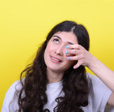 Portrait of woman crying and wiping tears against yellow backgro Stock Photography
