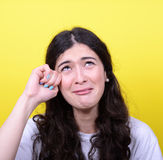 Portrait of woman crying and wiping tears against yellow backgro Stock Photos