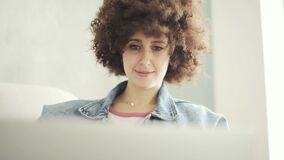 Portrait of woman with curly hair smiling and looking on laptop sitting on sofa.