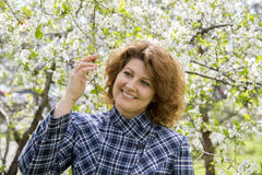 Portrait of  woman with curly hair in  cherry garden in spring Royalty Free Stock Images