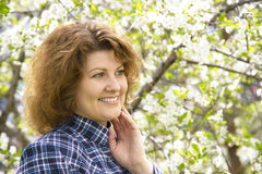 Portrait of  woman with curly hair in  cherry garden in spring Royalty Free Stock Photos