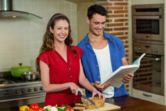 Portrait of woman cutting loaf of bread and man checking recipe book. Portrait of women cutting loaf of bread while men checking the recipe book in kitchen at Stock Image