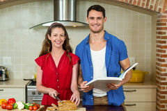 Portrait of woman cutting loaf of bread and man checking recipe book Royalty Free Stock Photo