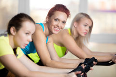 Portrait of woman cycling in gym stock photography