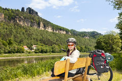 Portrait of woman cyclist resting on a bench in nature. Stock Photos