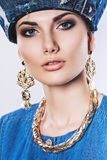 Portrait of woman in denim hat and golden earrings Stock Photos