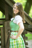 Portrait of woman in dirndl in front of wooden shack Royalty Free Stock Image