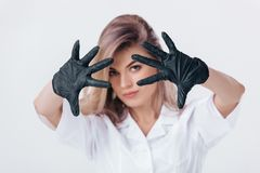 Woman doctor in black medical gloves shows stop sign. Portrait of woman doctor in black medical gloves shows stop sign royalty free stock image