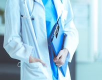 Portrait of woman doctor with folder at hospital corridor stock photography
