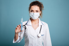 Portrait of woman doctor in mask standing and holding syringe Royalty Free Stock Image