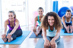 Portrait of woman doing forward bend pose with friends Royalty Free Stock Photography