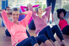 Portrait of woman doing sit ups with friends Stock Image