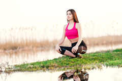 Portrait of woman doing yoga in nature. Beautiful young woman doing yoga sitting near the lake Stock Photography