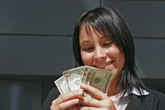 Portrait of woman with dollars. A portrait of a girl smiling downtown with dollars in a hand Royalty Free Stock Photo
