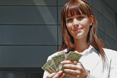 Portrait of woman with dollars. A portrait of a girl smiling downtown with dollars in a hand Stock Photography