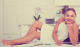 Portrait of woman in dress resting on table in office Stock Photography