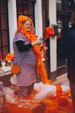Portrait of woman dressed in orange, crazy hat, selling junk on King`s Day festivity