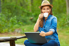 Portrait of woman drinking coffee and using laptop Stock Images